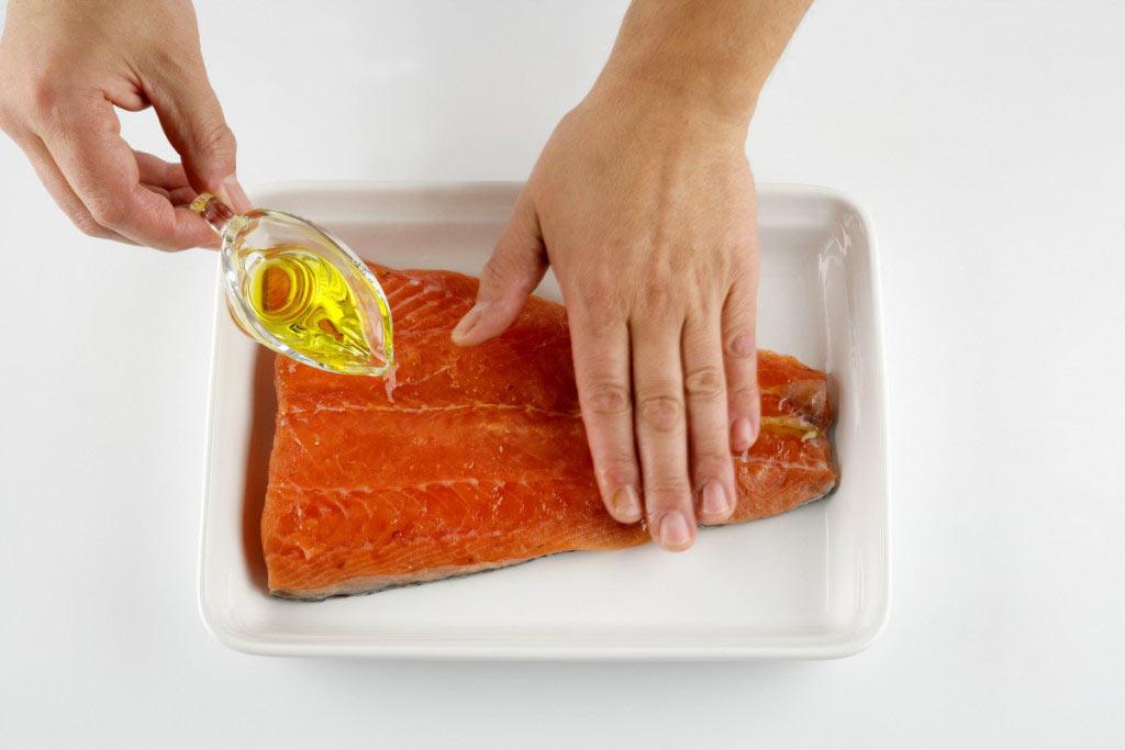 Regando el salmón con aceite de oliva (cenital)