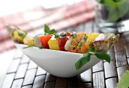 Brochetas de pescado con fruta y salsa pesto