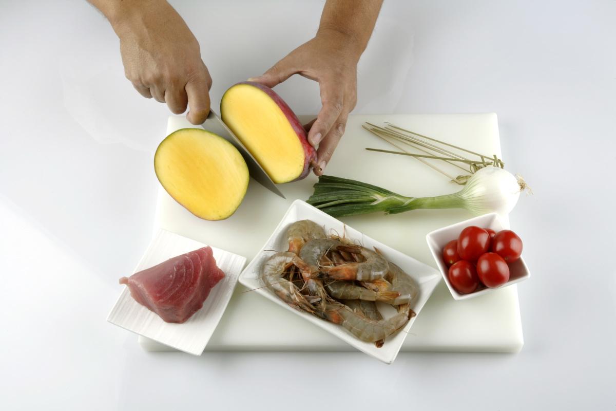 Pelamos la cebolleta y los langostinos. Cortamos en dados el mango y la cebolleta.