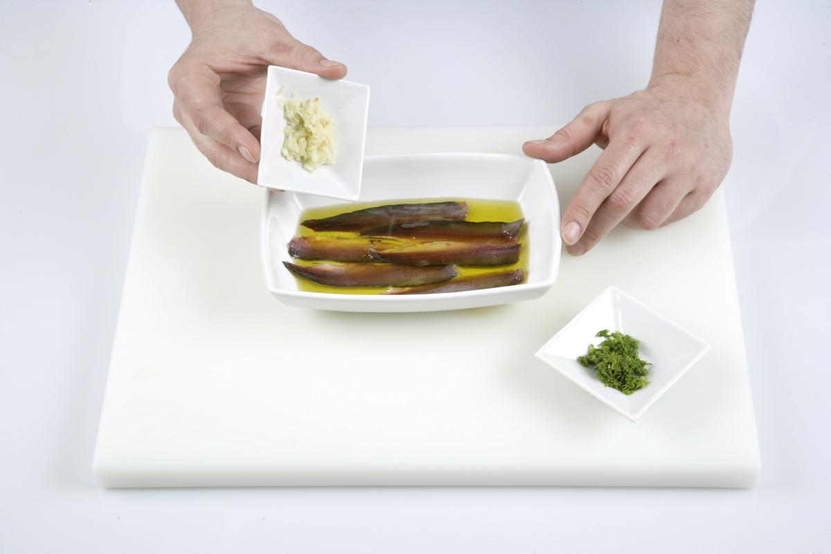 Cubrimos las sardinas con aceite de oliva, añadimos el ajo picado y las hojas de hinojo.