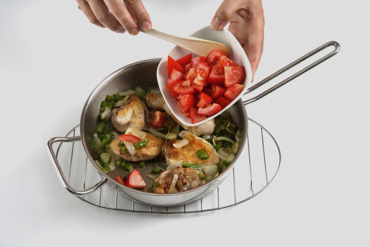 Añadimos el laurel y los tomates pelados y cortados en dados.