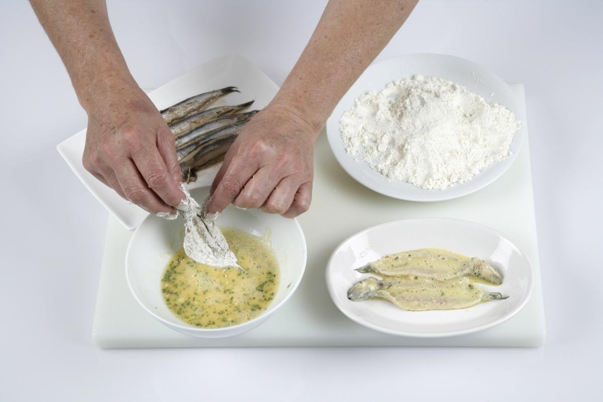 Pasamos los boquerones por harina, la mezcla de huevo, ajo y perejil.