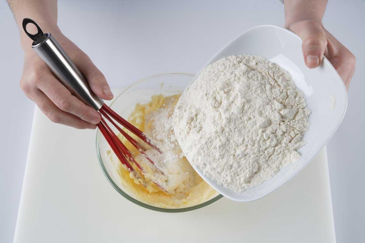 Espolvoreamos la harina tamizada con la levadura y mezclamos.