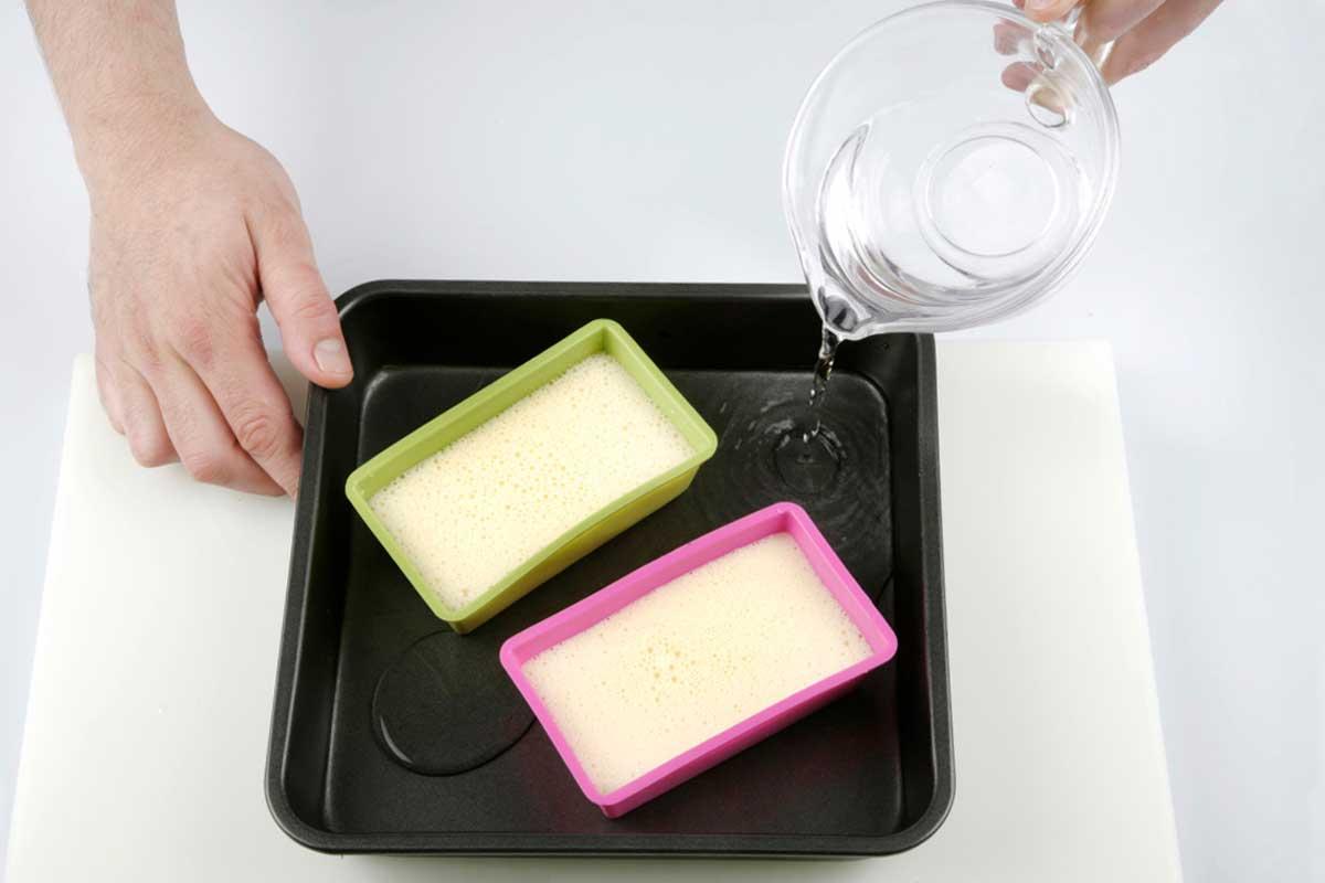 Colocamos los moldes en la bandeja de horno y llenamos con agua hasta cubrir parte de los moldes.