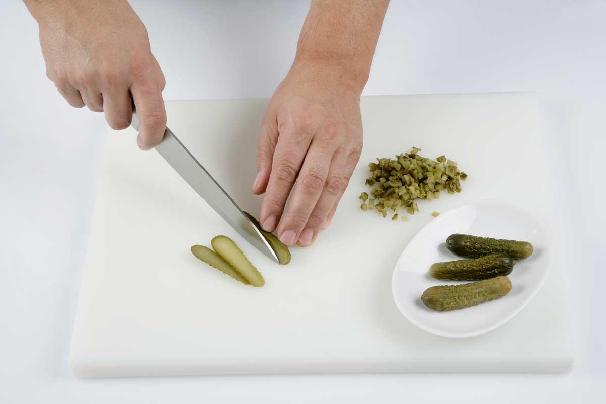 Picamos los pepinillos en vinagre.