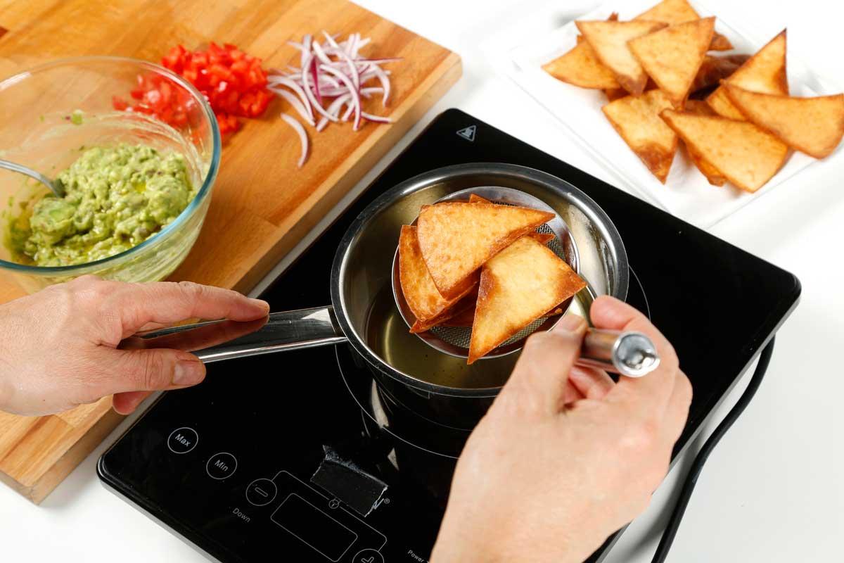 Cortamos las tortillas en triángulos y freímos.