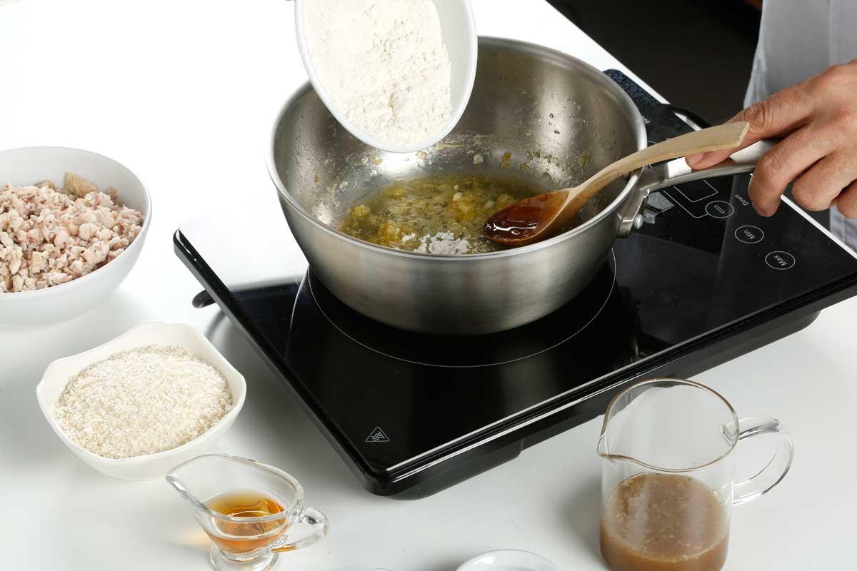 Introducimos en una olla el aceite, la mantequilla y la cebolleta picada.