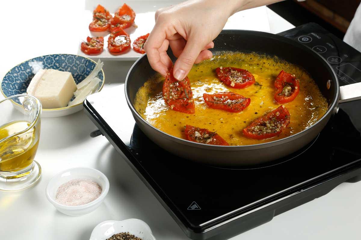 Batimos los huevos con un poco de sal y añadimos los tomates.