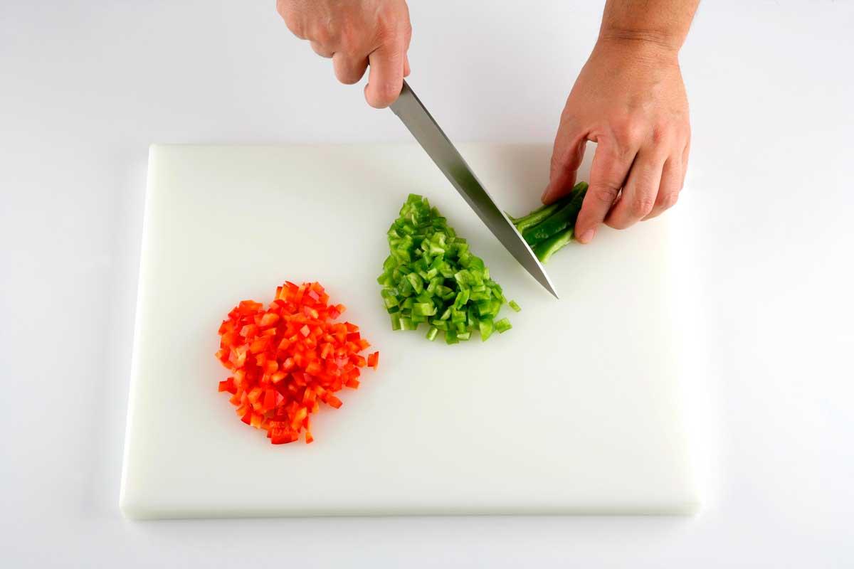 Cortamos los pimientos, el tomate y la cebolla.