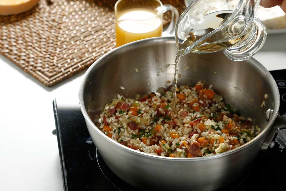 Agregamos el arroz y rehogamos. Incorporamos el vino y dejamos evaporar el alcohol.