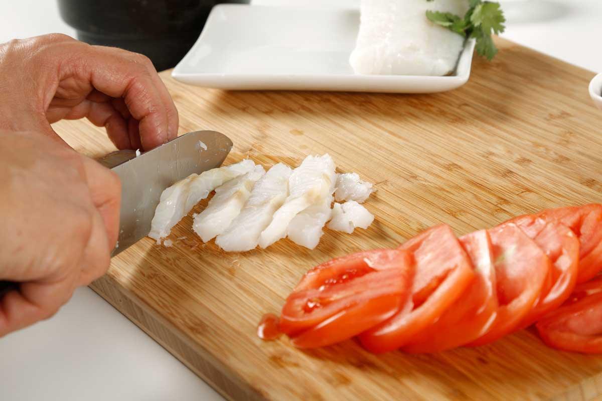 Cortamos los tomates y mezclamos con los pimientos y el bacalao.