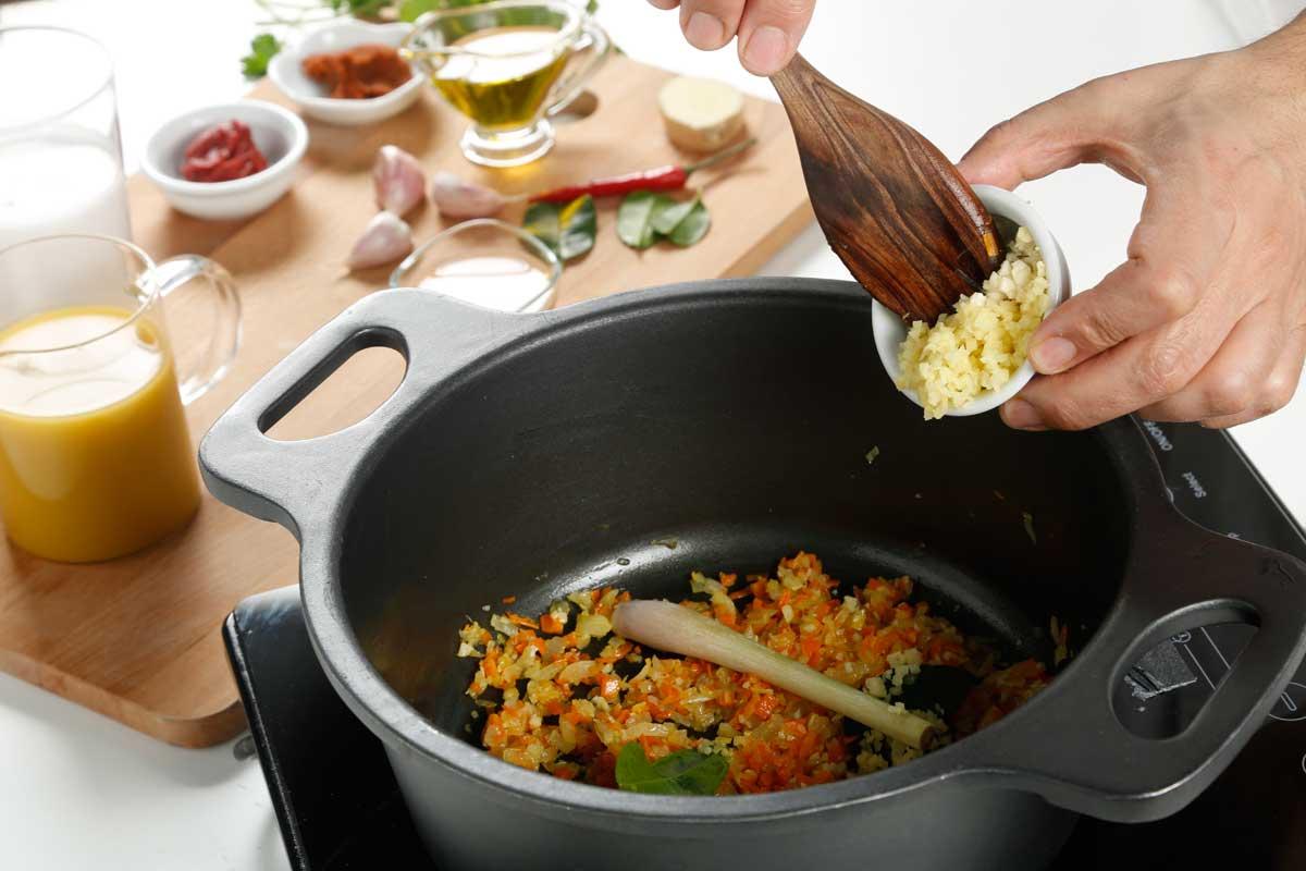 En una olla añadimos la cebolla, los ajos, la zanahoria, la citronela, las hojas de lima kaffir y el jengibre.