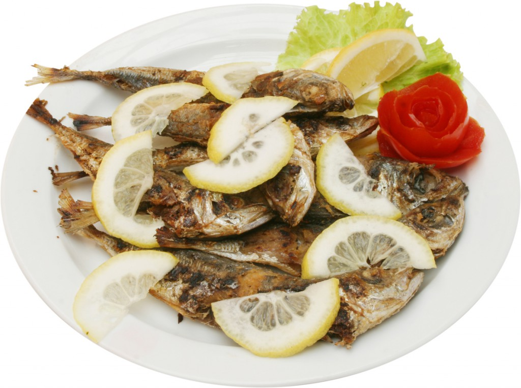 Grilled tasty fishes on barbecue with lemons and vegetables